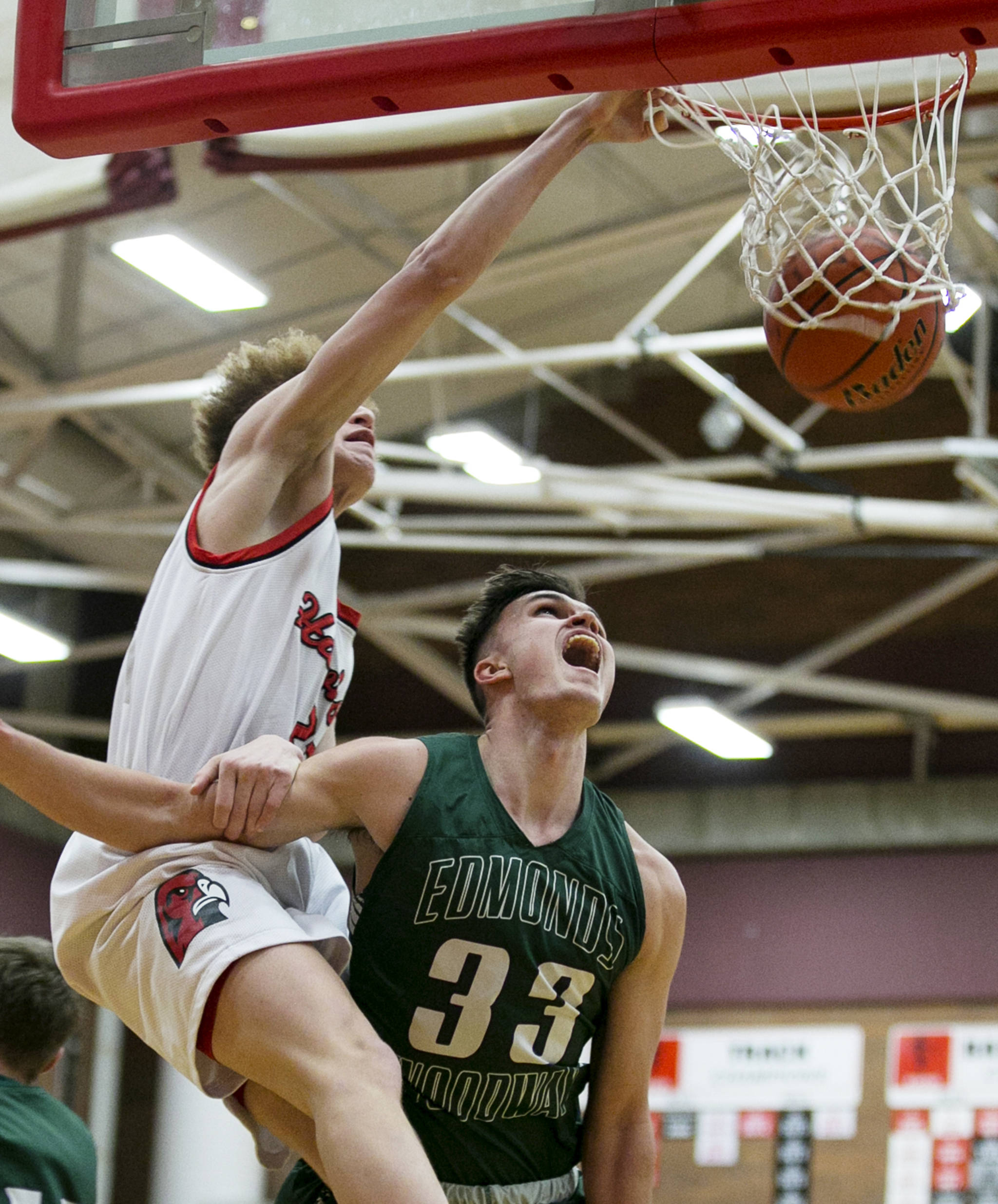 Mountlake Terrance's Khyree Armstead dunks and is fouled by Edmonds-Woodway's Kameron Eck at Mountlake Terrace High School on Jan. 23. (Kevin Clark / The Herald)