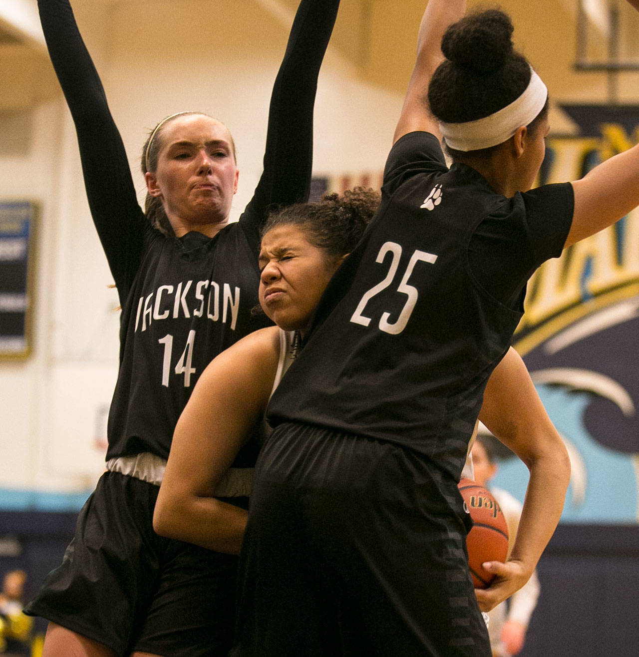 Mariner's Nia Hawkins drives with Jackson's Alexa Martin (left) and Sydney Carter defending during a Wesco 4A matchup Wednesday in Everett. Hawkins and the Marauders won 52-41. (Kevin Clark / The Daily Herald)