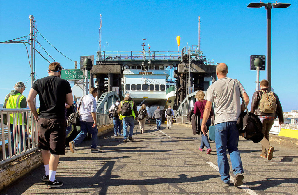 Commuters make their way to a ferry on the Mukilteo-Clinton run. (Kevin Clark / The Herald)
