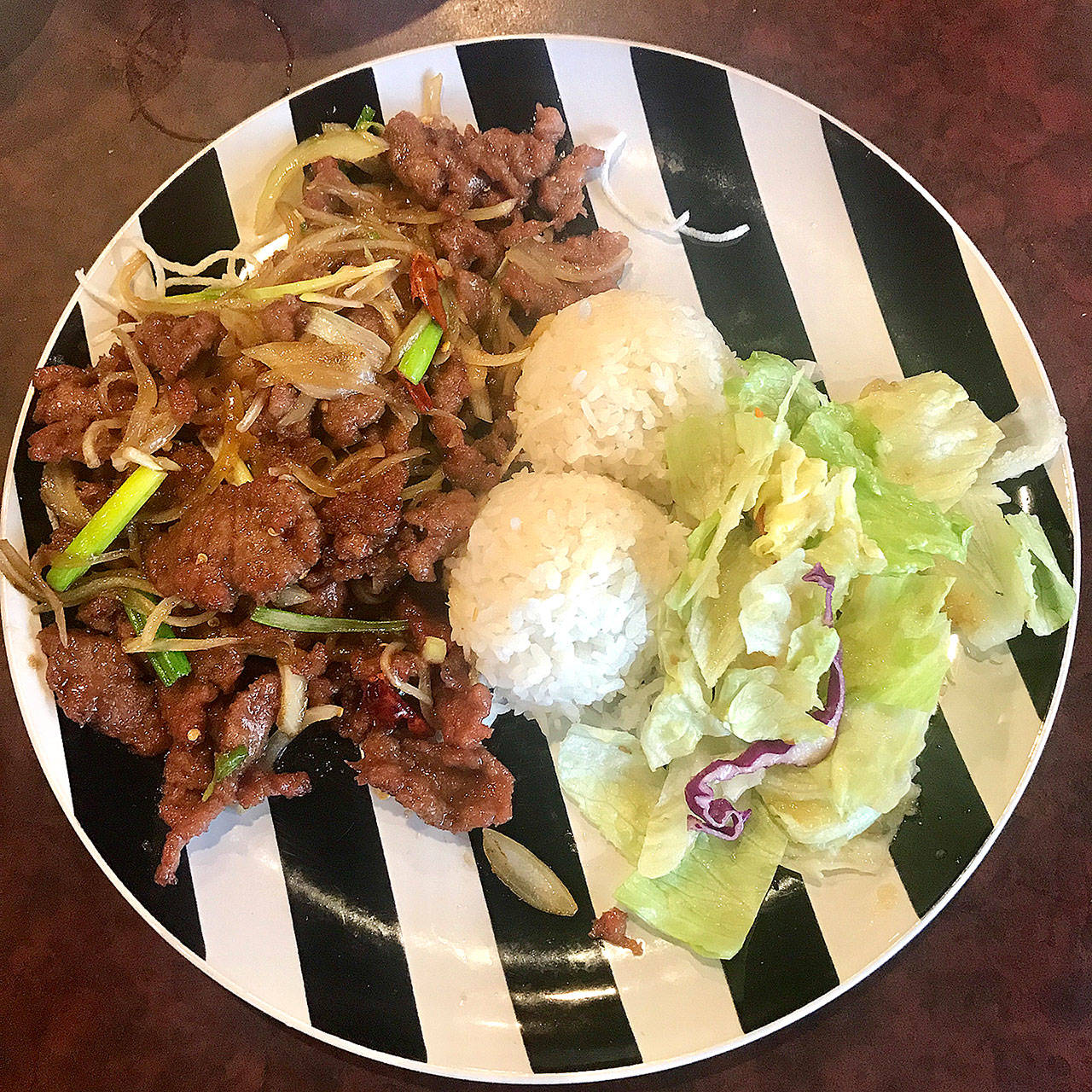 Mongolian beef is served with rice and salad for $8.95 at Umami Asian Cuisine in Mukilteo. (Andrea Brown/The Herald)