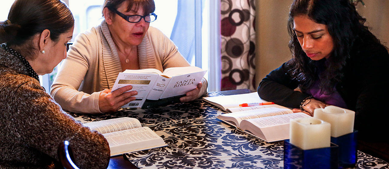 Faith Lutheran Church (of Everett) pastor Arhiana Shek (right) along with members Martha Schutten (left) and Fran Ulloa, holds a Bible study in Spanish at Ulloa's home in Lynnwood on Jan. 16. (Dan Bates / The Herald)
