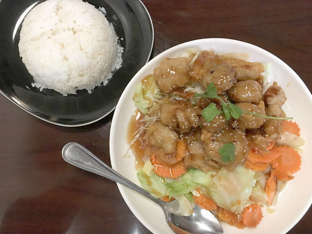 The crispy chicken lover comes with sliced carrot, cabbage, lettuce, and your choice of orange, sesame, or volcano sauce, with a side of jasmine rice at Bua Thai Fusion in Lake Stevens. (Ben Watanabe / The Herald)