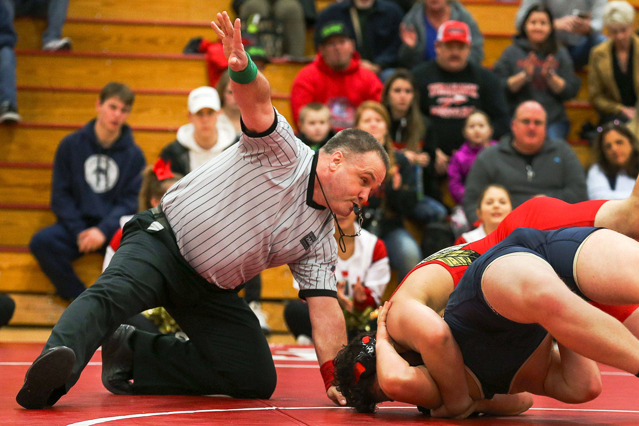 Match official Al Rivers signals to the scorer's table as Marysville Pilchuck's Ikaika Nawelhi looks to pin Arlington's Connor Stockman on Jan. 25 in Marysville. (Kevin Clark / The Daily Herald)