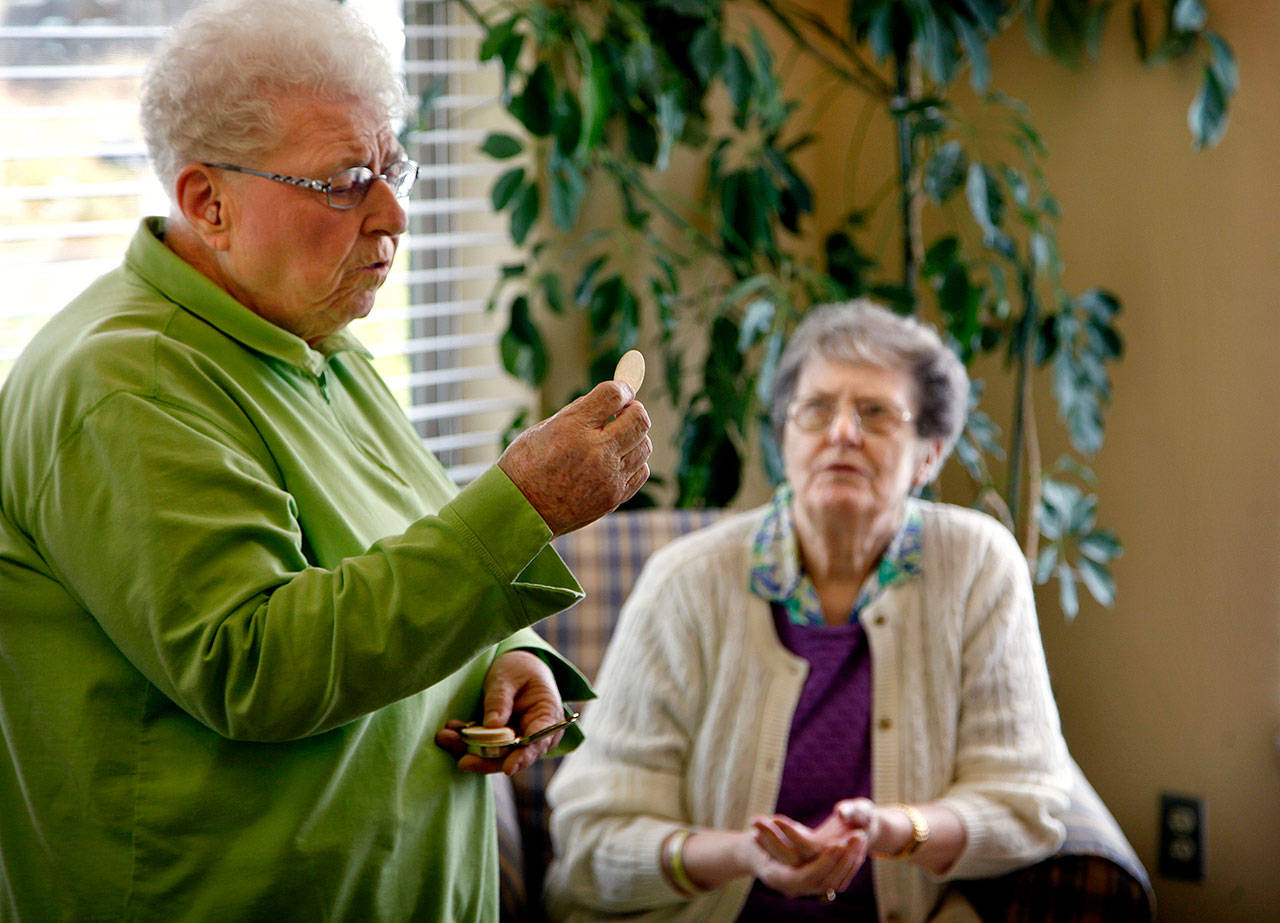 In July 2012, Sister Barbara Geib (left) of St. Mary of the Valley Catholic Church in Monroe delivers Communion to seniors and residents, including Alice Beach (back) at Regency Care Center in Monroe. At the time, Geib was celebrating her 60th year as a nun. (Dan Bates / The Herald)