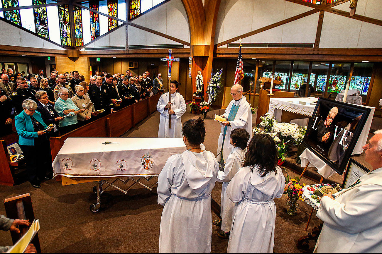 At a funeral Mass for Sister Barbara Geib at St. Mary of the Valley Catholic Church in Monroe Thursday, the Rev. Phillip Bloom officiates as police, firefighters, nuns from Geib's religious order and others listen and take part. Geib, a parish sister at the church, was Monroe's first police chaplain. (Dan Bates / The Herald)