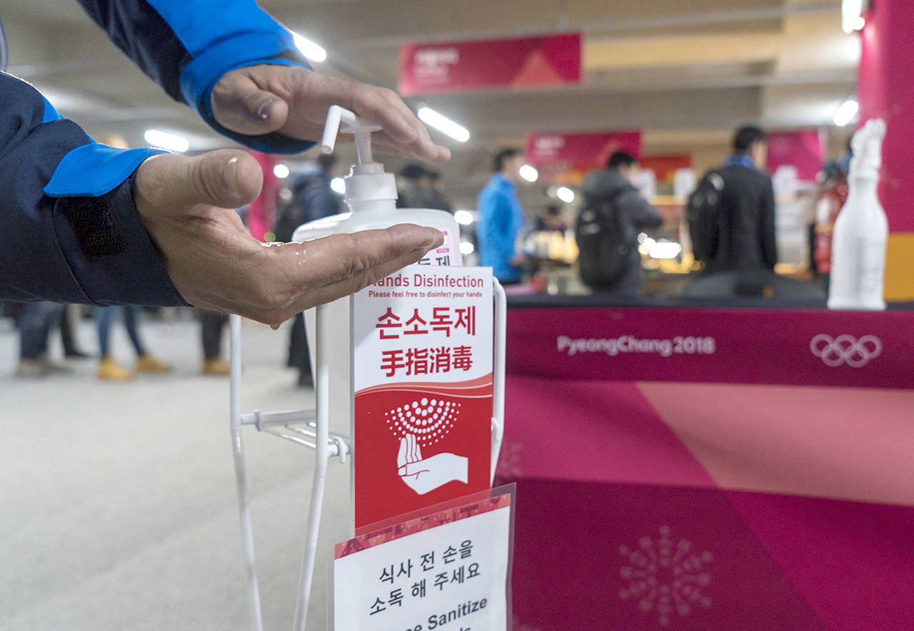 A man sanitizes his hands at the entrance to the media cafeteria in Gangneung, South Korea, on Wednesday. (Paul Chiasson/The Canadian Press via AP)