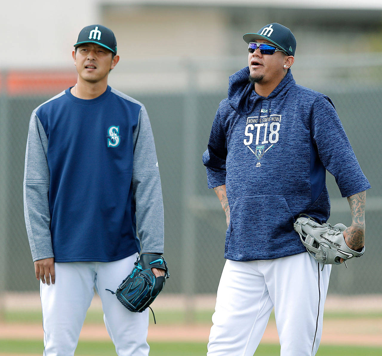 Seattle's Felix Hernandez (right) and Hisashi Iwakuma watch a drill during spring training on Monday in Peoria, Ariz.(AP Photo/Charlie Neibergall)