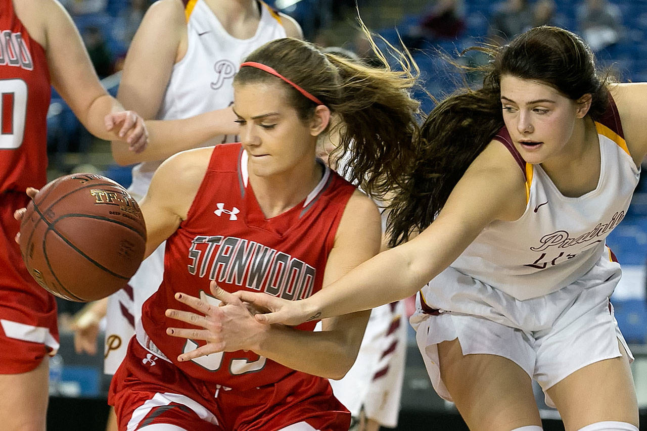 Stanwood's Ashley Alter (left) gathers a loose ball with Prairie's Mallory Williams reaching in during a 3A Hardwood Classic game on Feb. 28, 2018, at the Tacoma Dome. (Kevin Clark / The Herald)