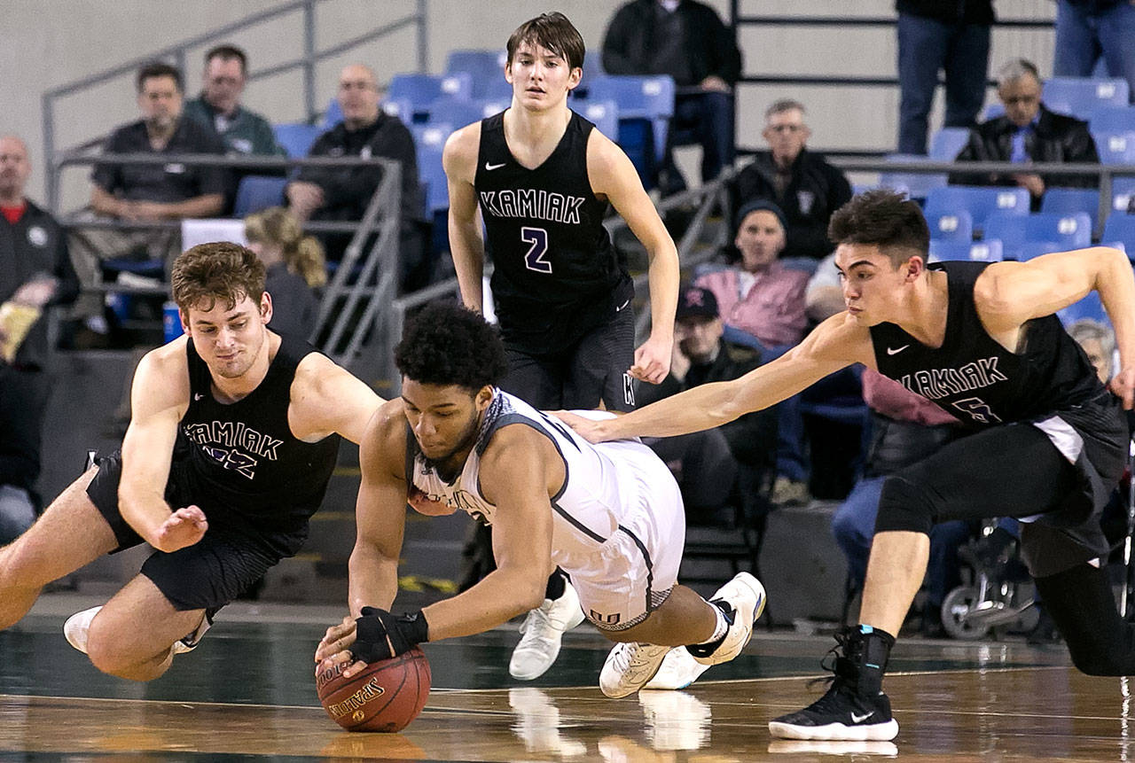 Union's Alishawuan Taylor (center) and Kamiak's Braden Leary dives for a loose ball with Kamiak's Patrick Olson (right) and Kamiak's Dakota Bueing (standing ) looking on during the WIAA state basketball tournament Wednesday at the Tacoma Dome in Tacoma on February 28, 2018. (Kevin Clark / The Daily Herald)
