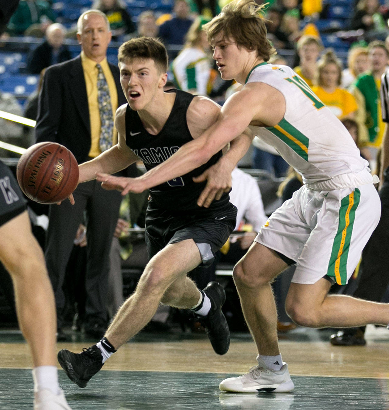 Kamiak's Carson Tuttle drives with Richland's Cody Sanderson defending during a 4A boys Hardwood Classic game on March 1, 2018, at the Tacoma Dome. (Kevin Clark / The Herald)