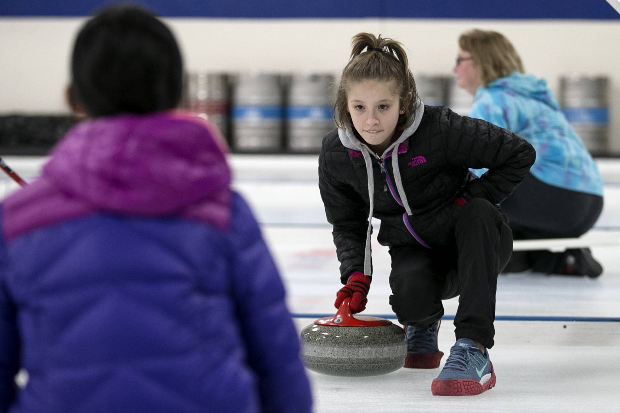 Sole Norman (right) practices rotating a rock to Ruby Kerwin during open house at the Granite Curling Club in Seattle on Feb. 18. (Kevin Clark / The Herald)