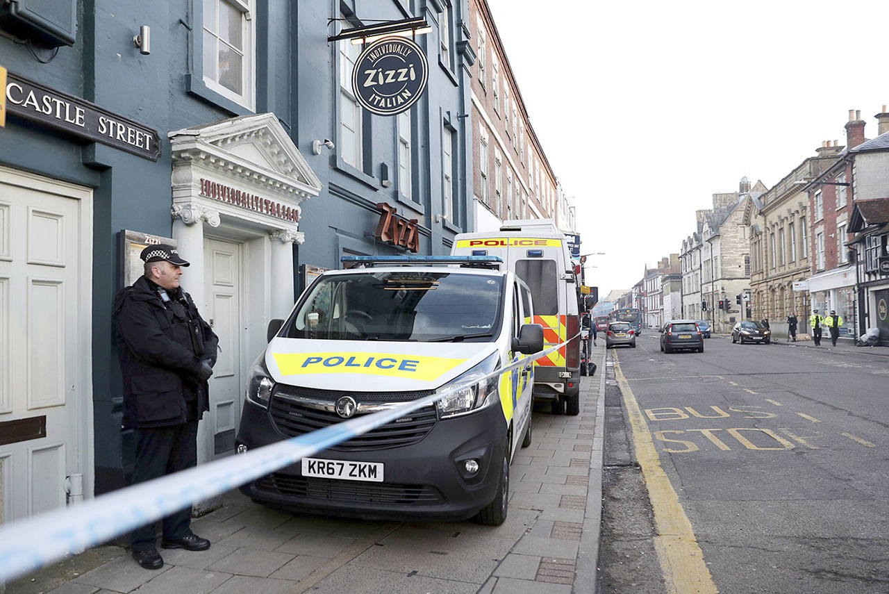 A policeman stands outside the Zizzi restaurant in Salisbury, England on Wednesday, near to where former Russian double agent Sergei Skripal was found critically ill. (Andrew Matthews/PA via AP)