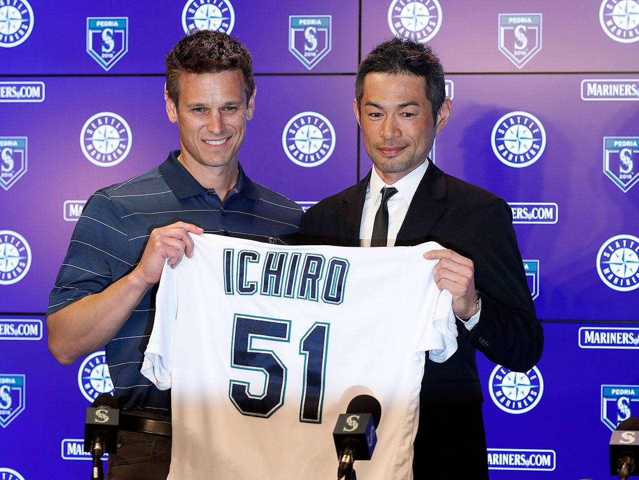 Ichiro Suzuki (right) holds up his jersey with Mariners' general manager Jerry Dipoto during a news conference at the teams' spring training complex on Wednesday in Peoria, Ariz. Ichiro, who starred in Seattle from 2001 until he was traded in 2012, signed a one-year deal to return to the Mariners. (AP Photo/Matt York)