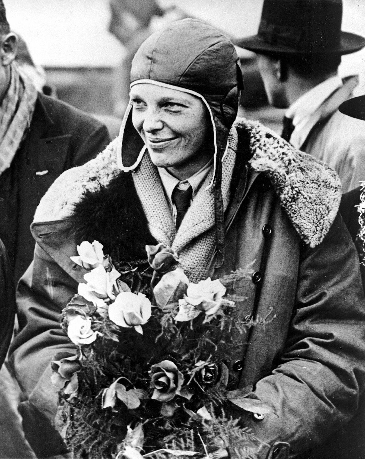 "In a June 26, 1928 photo, American aviatrix Amelia Earhart poses with flowers as she arrives in Southampton, England, after her transatlantic flight on the ""Friendship"" from Burry Point, Wales. (AP Photo, File)"