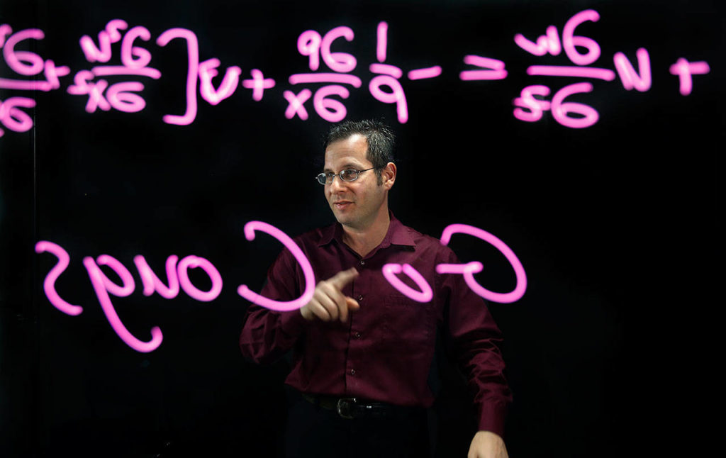 """At WSU Everett, Professor Gordon Taub pre-records many of his lectures and publishes them on-line so his students can get into the subject matter and raise questions to him one-on-one if they need help. To accomplish this, he uses a """"lightboard studio"""" which allows him to face the camera and write lessons or other messages on a large, thick glass surface. Stratigic lighting, and a black backgroung make the content stand out. A video camera records everything and the image is flipped horizontally so symbols and messages are not backwords. (Dan Bates / The Herald)"""