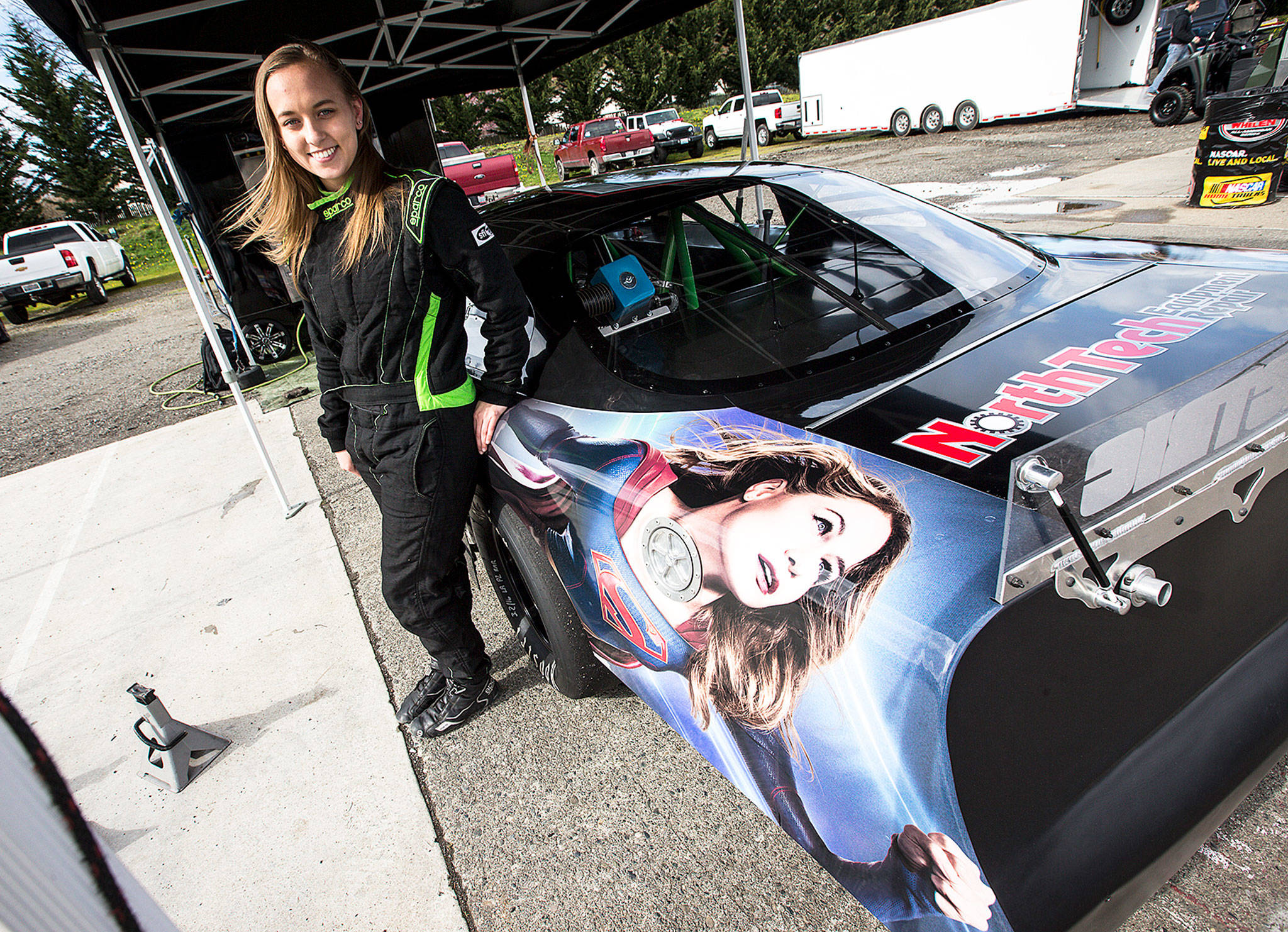 """Brittney Zamora stands next to her """"Supergirl"""" Super Late Model race car at the Evergreen Speedway. (Ian Terry / The Herald)"""