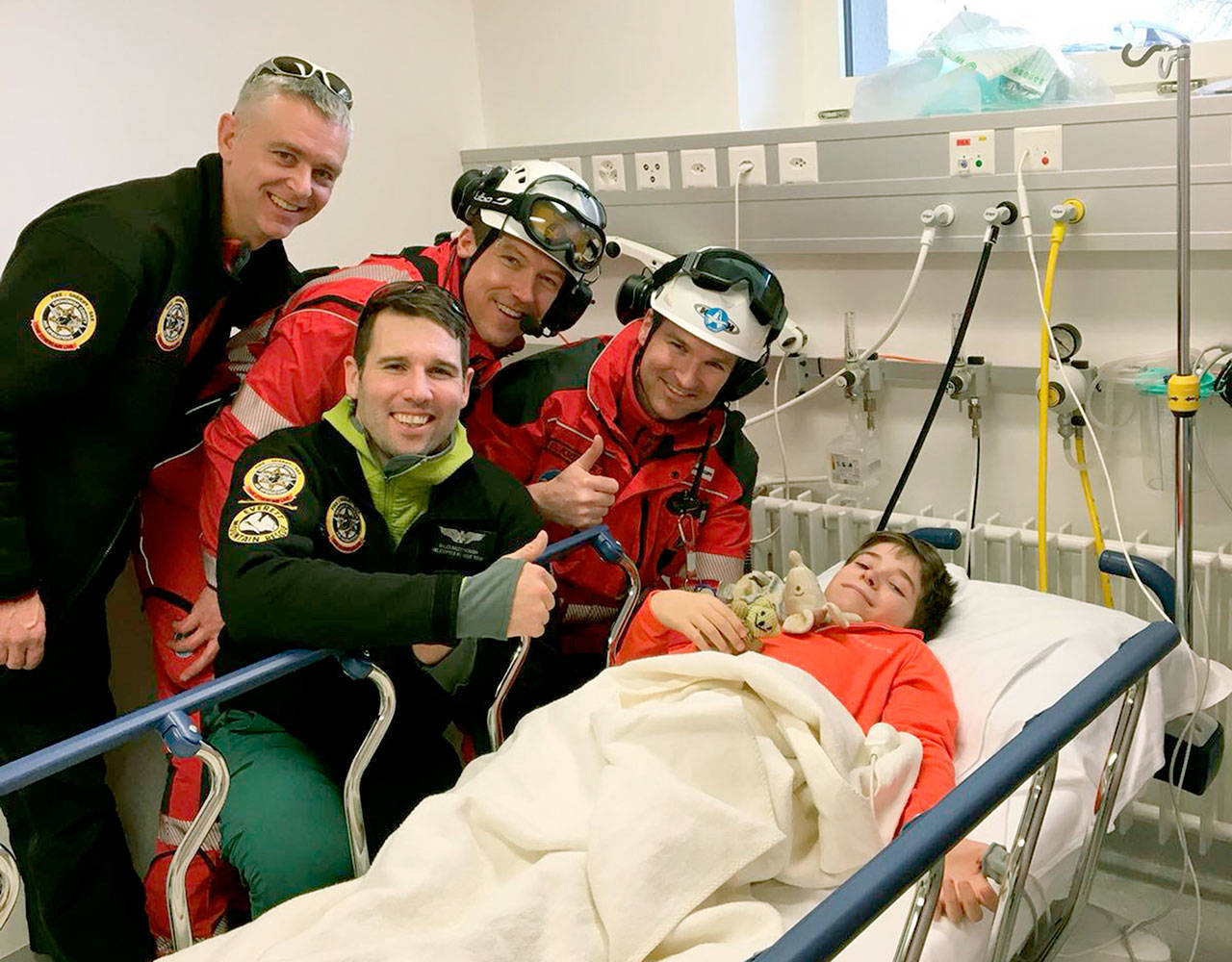Richard Duncan (left) and Miles Mcdonough (second from left) of the Snohomish County Sheriff's Office helicopter rescue team pose with Swiss helicopter crew members Peter Lackermeier (third from left) and Oliver Kreuzer with the boy they helped rescue after a skiing accident on Rothorn mountain in Switzerland.