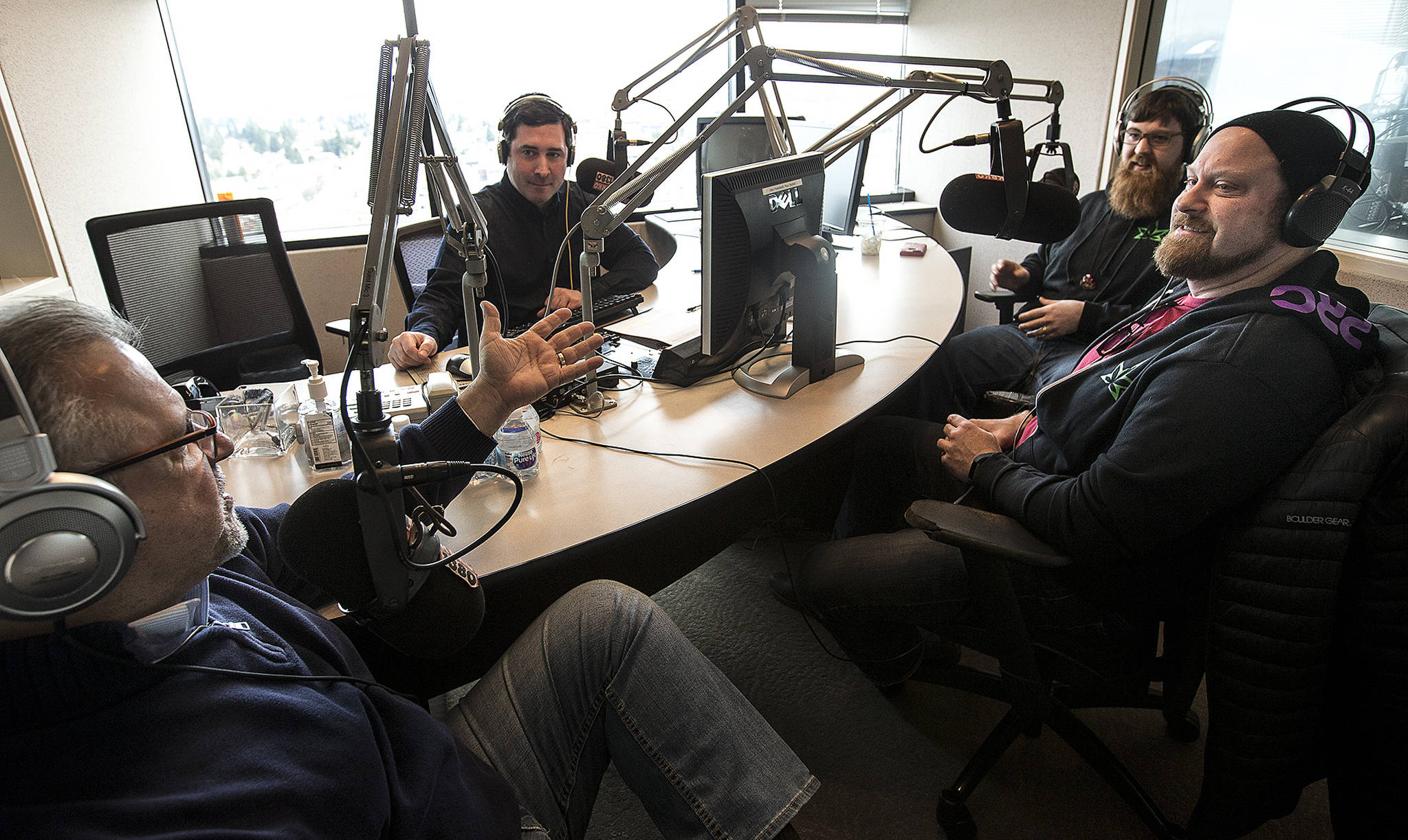 "A podcast episode of ""In the Weeds"" is recorded with hosts Maury Eskenazi (left) and Tavis Buchan (center left) and guests from PRC marijuana shops Thomas Fallihee (center right) and Joel Martin (right) at the KRKO/KXA radio station offices in downtown Everett. The talk show style podcast explores issues within the marijuana industry in Washington and beyond. (Ian Terry / The Herald)"