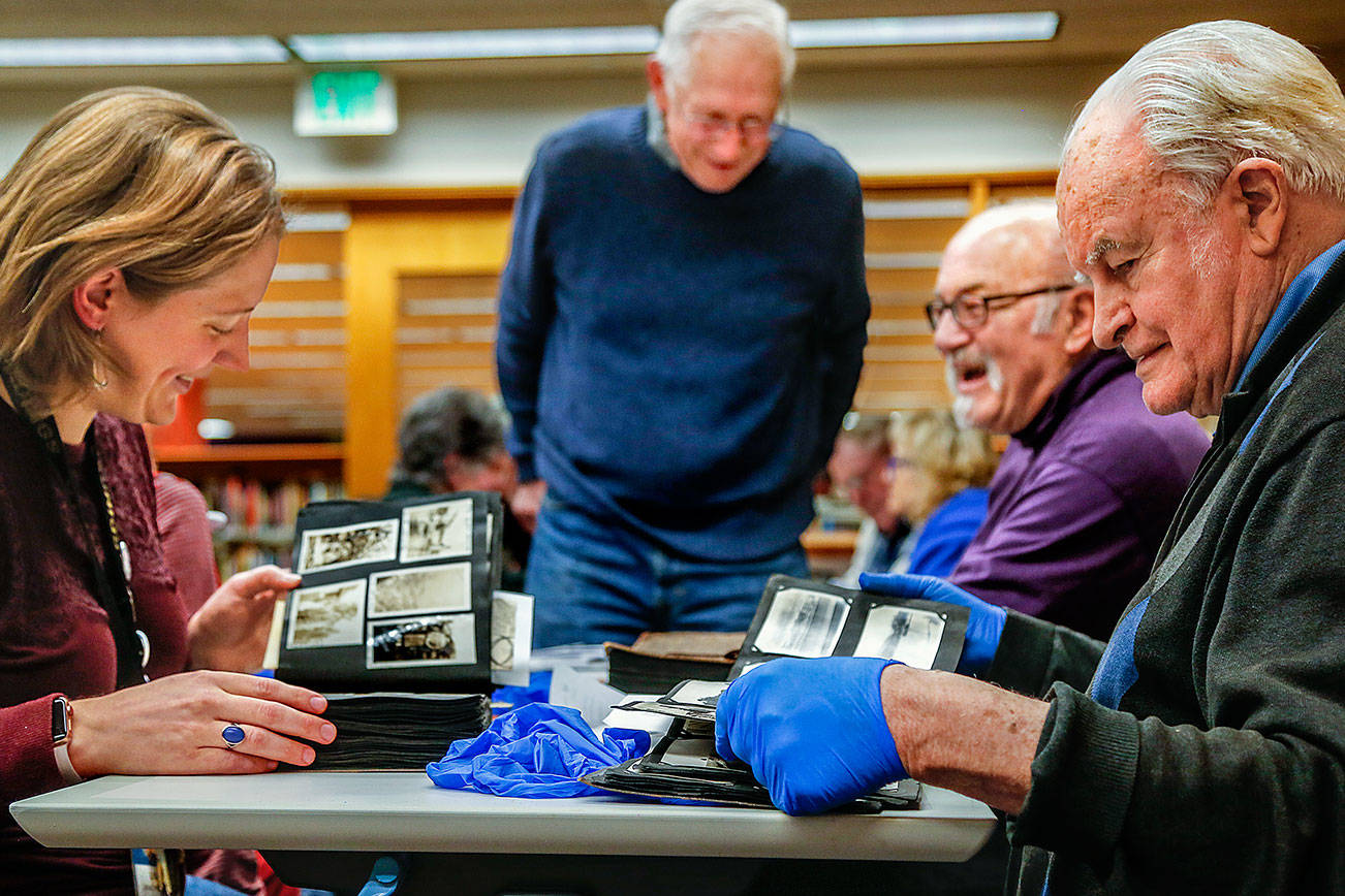 From left, library historian Lisa Labovitch, Jerry Solie (standing), and history buffs Dave Ramstad and William Vincent (right) enjoy one another's light conversation while studying images in dozens of scrapbooks and photo albums Tuesday night at the Everett Public Library. (Dan Bates / The Herald)