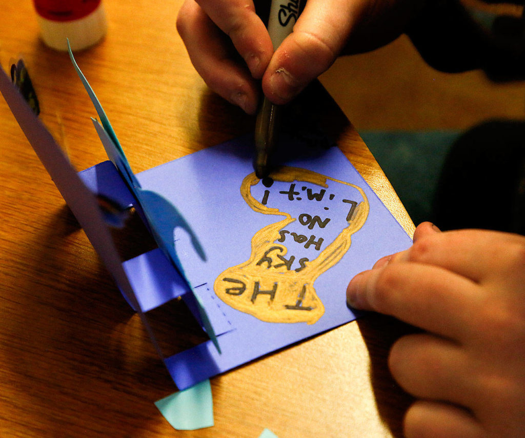 Brayden Whetstine, 12, from Haller Middle School, applies finishing touches to the pop-up card he created with his message. (Dan Bates / The Herald)