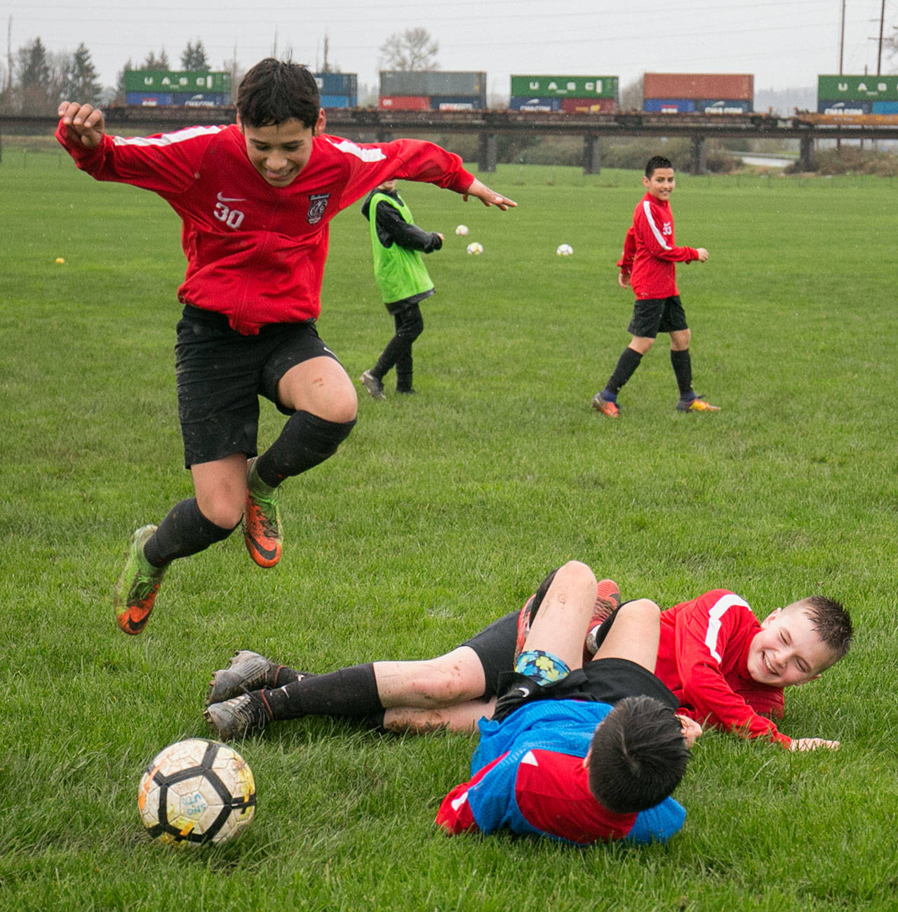Gerardo Avalos-Ayala (left) hurdles over Cason Chadd (top) and Acxel Gonzalez-Lara (bottom) after the latter two players collided during a Snohomish Youth Soccer Club Development Academy scrimmage at Stocker Fields on April 5 in Snohomish. (Kevin Clark / The Daily Herald)