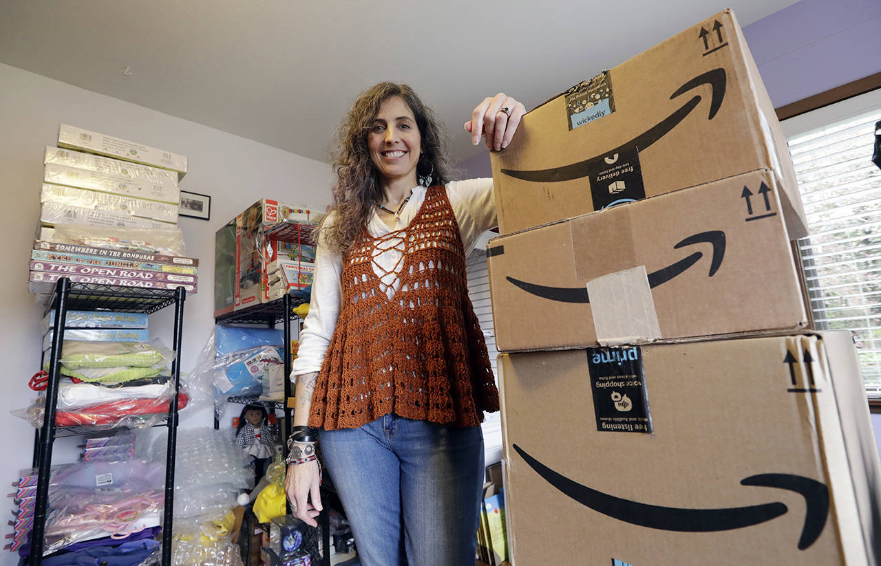 Adrienne Kosewicz, owner of Seattle-based Play It Safe World Toys, pays $3,600 a year for tax collection software to handle payments and reports to the state. She sells through Amazon, which handles computation and collection. (AP Photo/Elaine Thompson)
