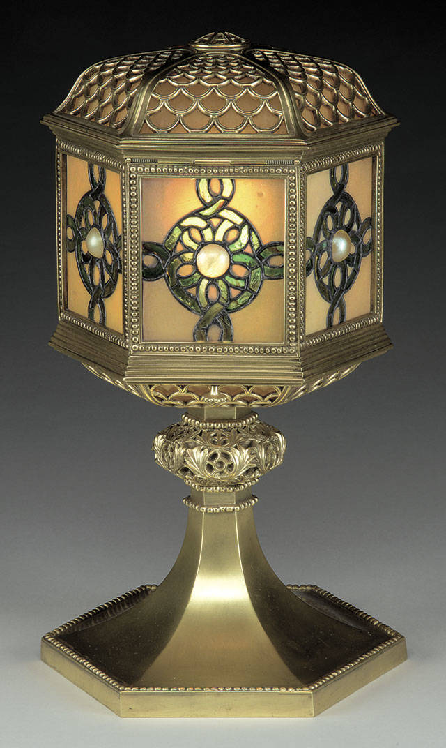 "This 15½-inch-tall table lantern marked ""Tiffany Studios New York"" sold for $6,655 at a recent James D. Julia auction in Maine. It has a shade with glass panels centered with a cabochon jewel. The stem is decorated bronze with a gold patina. (Cowles Syndicate Inc.)"