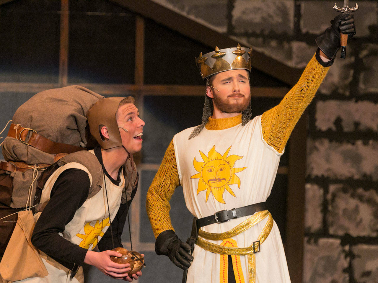 """Gavin McKeever (left) as Patsy looks on a Aidan Norris as King Arthur raises Excalibur during Kamiak High School's production of """"Spamalot."""" (Kevin Clark / The Herald)"""