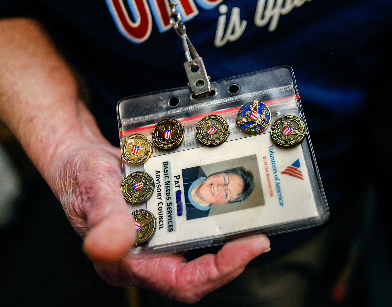 Volunteer Pat Reeve, 78, has seven pins on her VOA identification card for helping many hours. (Dan Bates / The Herald)