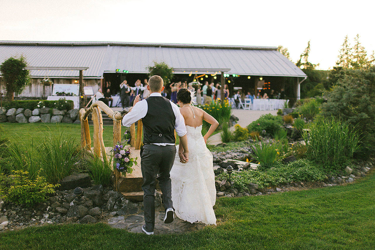 A groom and bride run over a bridge at Swan Trail Farms in Snohomish. (Rhys Logan Photography)