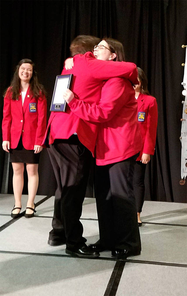 Arlington High School culinary arts teacher Teri Bravomejia hugs her son Henry during the SkillsUSA Washington State Conference. Bravomejia was recognized as the SkillsUSA Washington Advisor of the Year. (Contributed photo)