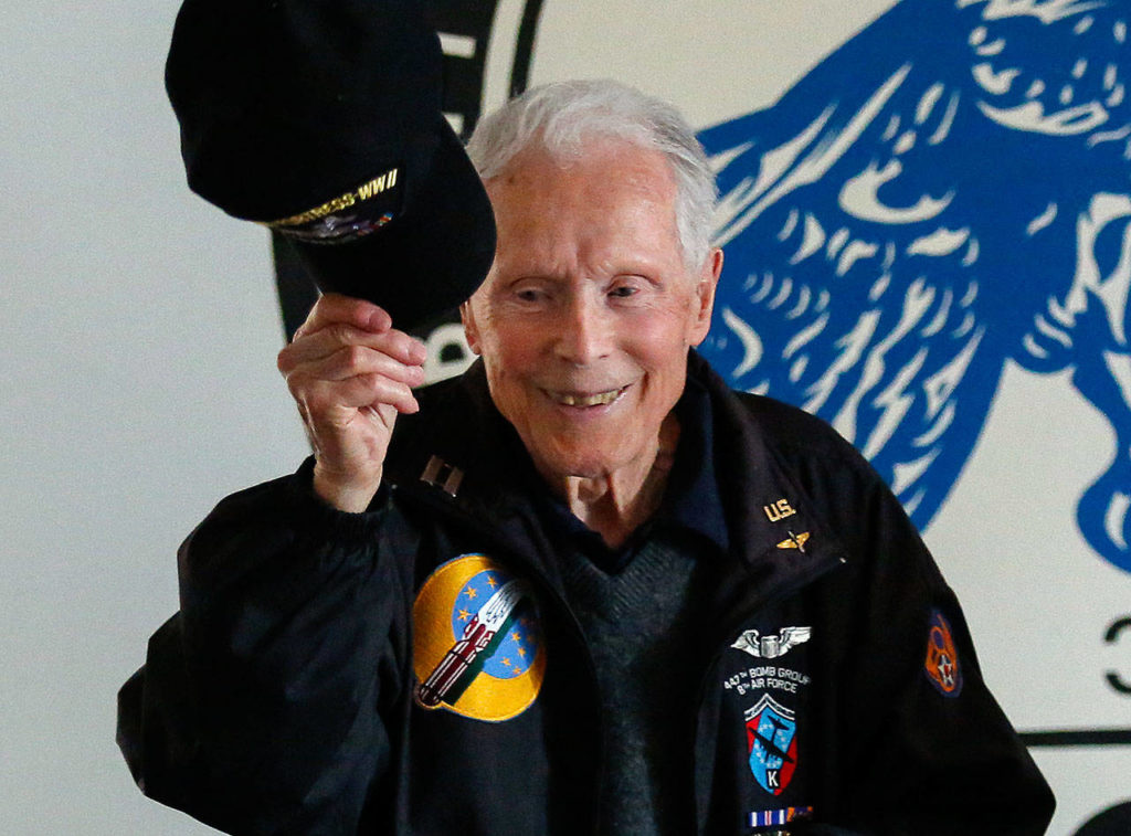 At the conclusion of his talk, 95-year-old Dick Nelms, who flew 35 missions in B-17 bombers in World War II, tips his cap to appreciative fellow military pilots at the Stanwood Eagles Thursday. (Dan Bates / The Herald)