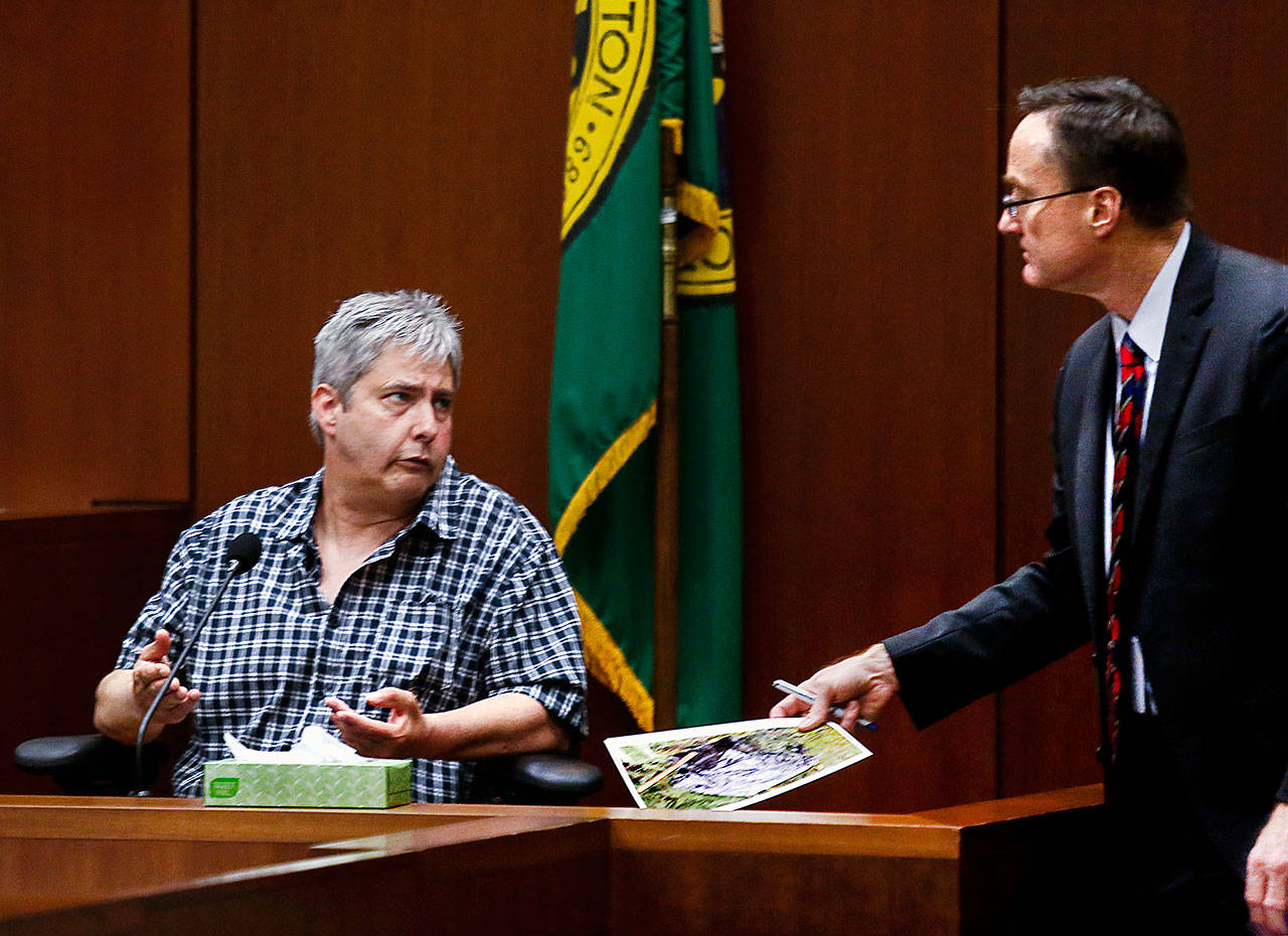 After showing Tony Reed (left) an evidence photo Tuesday, Snohomish County chief deputy prosecutor Craig Matheson listens as Reed testifies. (Dan Bates / The Herald)