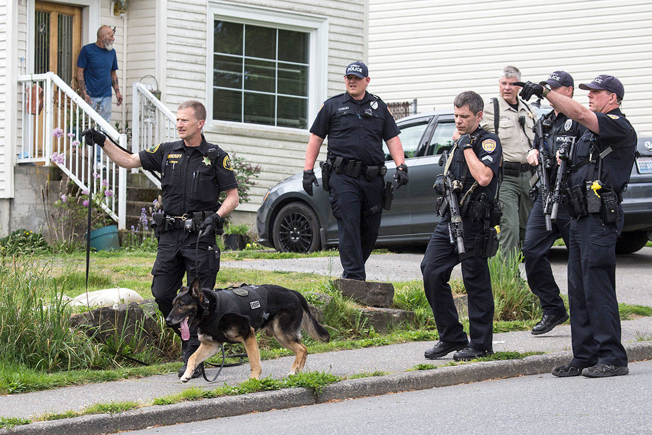 Everett police officers and a K-9 unit from the Snohomish County Sheriff's Office search for the suspect in a shooting at the Farwest Motel on Wednesdayin Everett. (Andy Bronson / The Herald)