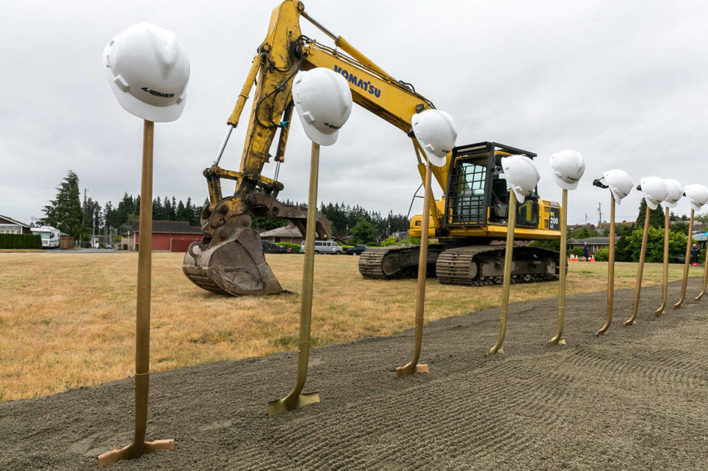 Hard hats, shovels and a backhoe decorate the site of the new Everett Family YMCA Saturday morning. (Kevin Clark / The Herald)