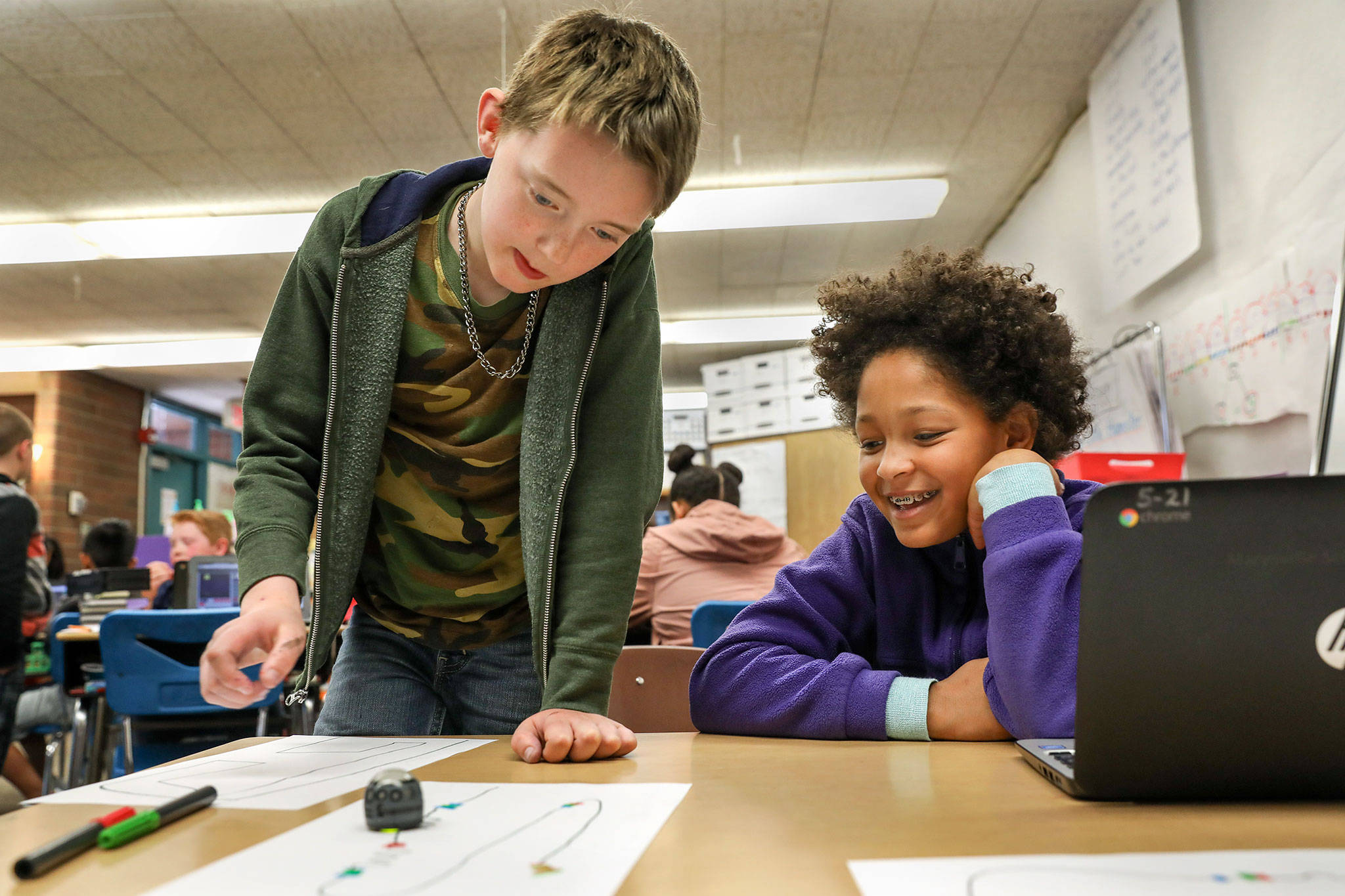 Gavin Dyche (left) and Ayla Martin, third grade students at Pinewood Elementary School in Marysville, learn to direct a robot though code using a Chromebook on May 15, 2018. (Lizz Giordano / The Herald)