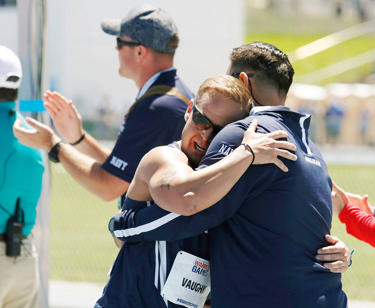Navy Chief Petty Officer Tim Vaughn (left), of Marysville,	hugs track coach Kyle Putnam (right) after Vaughn competed in the men's 1500 meters at the U.S. Air Force Academy near Colorado Springs, Colorado, on	June 2 . Vaughn is an athlete competing in the ninth edition of the Department of Defense Warrior Games. (Photo/Zoe L. Smith, Grady Sports Bureau)