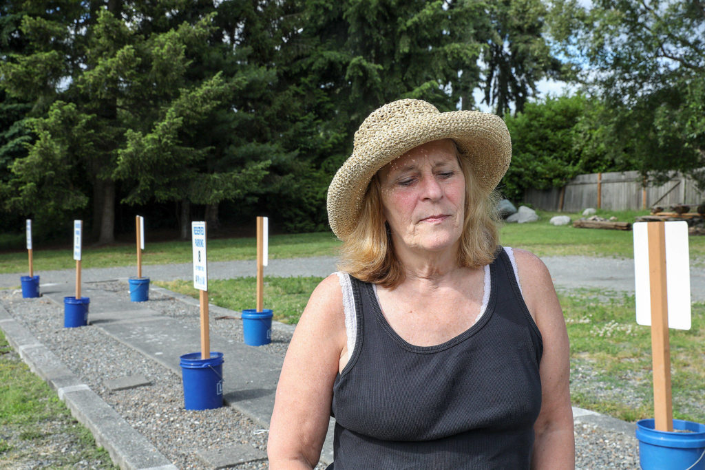 Michele Dana, who lives in her vehicle, is part of a safe parking program hosted by the Edmonds Unitarian Universalist Church. The church provides 10 spots, pictured behind Dana, to families and single women. (Lizz Giordano / The Herald)
