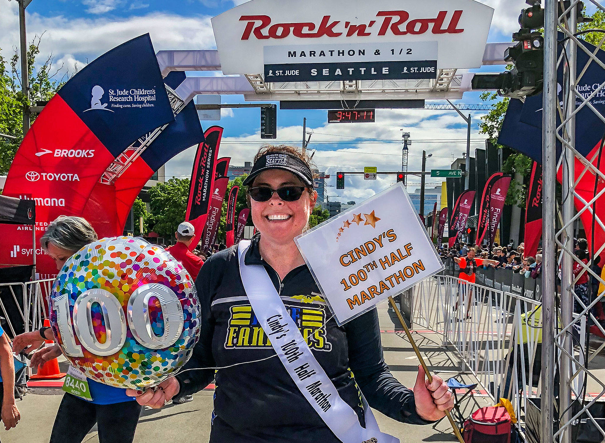 Lynnwood's Cindy Ward, 42, completed her 100th half marathon earlier this month. Here, she celebrates at the finish line of the Rock 'n' Roll Seattle Half Marathon at Seattle Center. (Photo courtesy Cindy Ward and Gretchen Tapp)