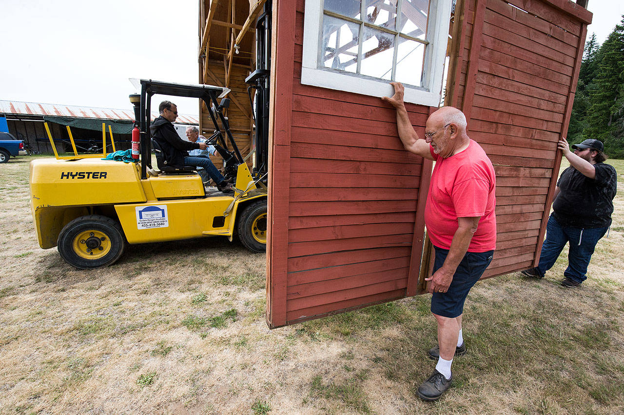 Volunteers, Bruce Angell, on forklift, Ralph Frazier, Pat Connelly, in red, and Roland Shaw move a section of the red barn to its new position at the Arlington Airport, in preparation for the Arlington Fly-In. The barn is the centerpiece of a historic airplane exhibit during the airshow event. (Andy Bronson / The Herald)