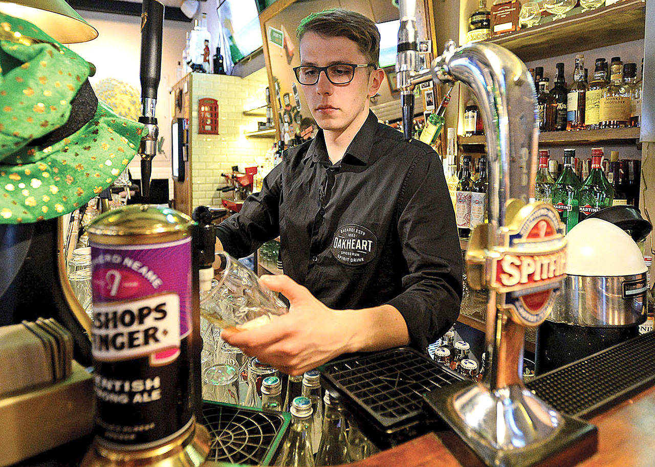 "Bartender Mateusz Molenda fills a glass of beer in a British pub in Warsaw, Poland, in 2017. Bartenders, not concierges, often know the full scoop on a city's ""hot"" and ""not"" spots. (Alik Keplicz/AP)"