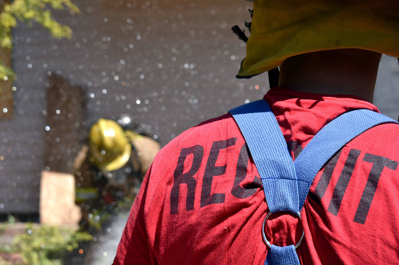Recruits practice with a firehose during a mock house fire on May 23 as part of Snohomish County's first fire academy. (Caleb Hutton / The Herald)