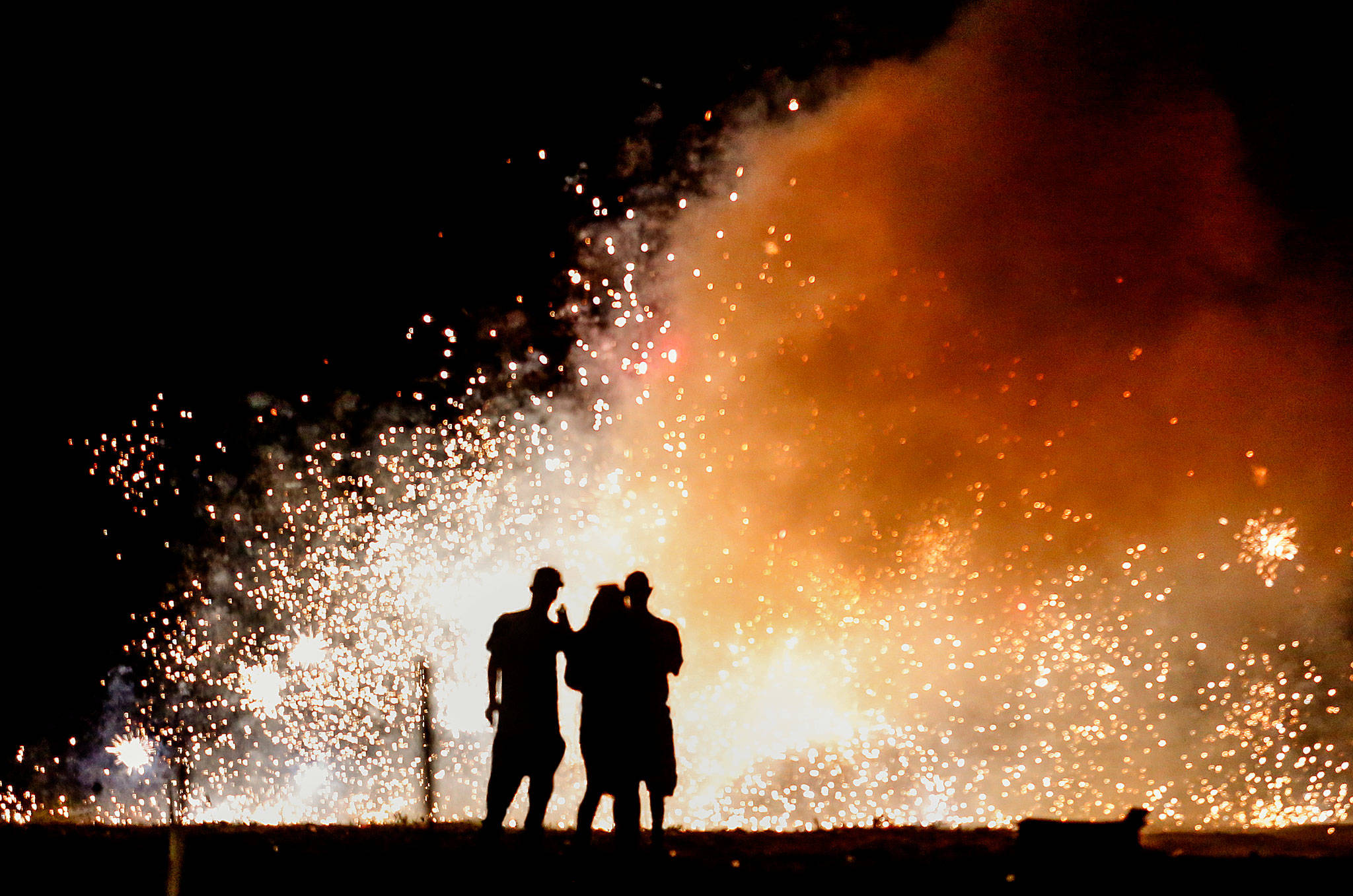 A trio in the lighting area at Boom City watches a shower of white-hot sparks from several fountains set off Tuesday just as darkness falls. (Dan Bates / The Herald)