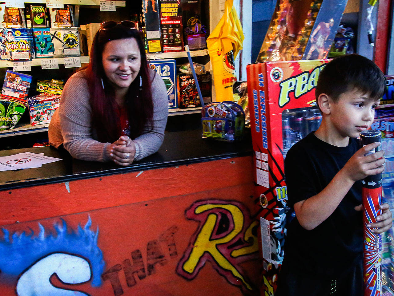 Eliza Davis, 37, smiles as she watches her 6-year-old nephew, Micah Thornberry, take a confetti blaster she gave him to pop open with another youngster outside her stand, Fireworks that Rock. At 10, Davis began selling fireworks with her parents. She now serves on the tribes' Boom City Committee. (Dan Bates / The Herald)