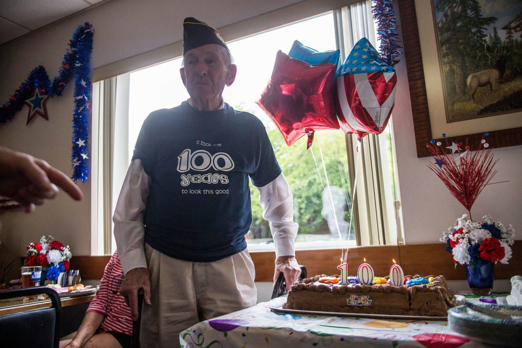 Edgar Shepherd stands next to his birthday cake during his 100th birthday celebration at the Lynnwood Elks Lodge on Wednesday. (Olivia Vanni / The Herald)
