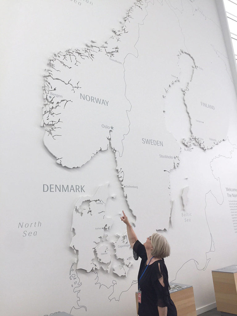 The author's mother, Betty Swaney, points to where her family emigrated from near Bergen, Norway, on the large map of Scandinavia at the Nordic Museum in Ballard. (Aaron Swaney)