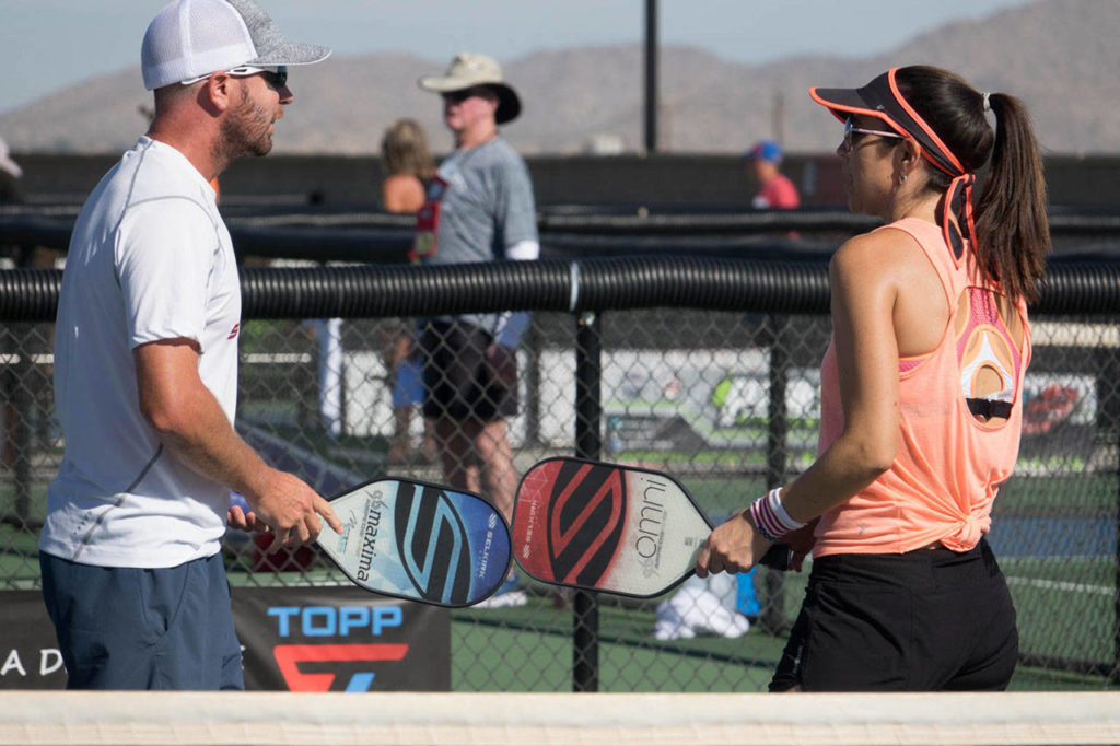 Tonja Major (right) and her mixed doubles partner discuss strategy during a pickleball match. (Selkirk Sport)