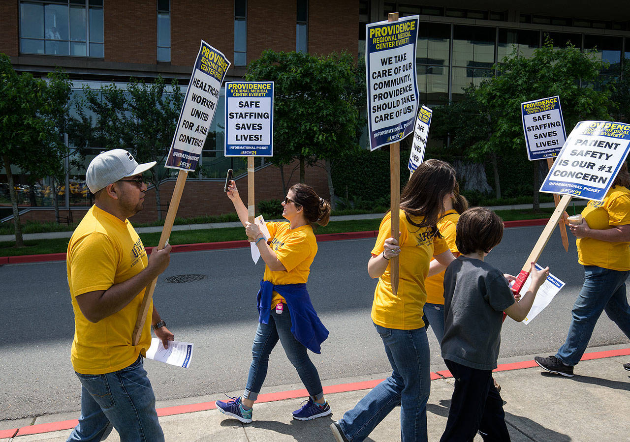 Nurse Amber Palermo, and a member UFCW 21, takes video of picketers and their supporters outside Providence Regional Medical Center Everett on June 6. (Andy Bronson / The Herald, file)