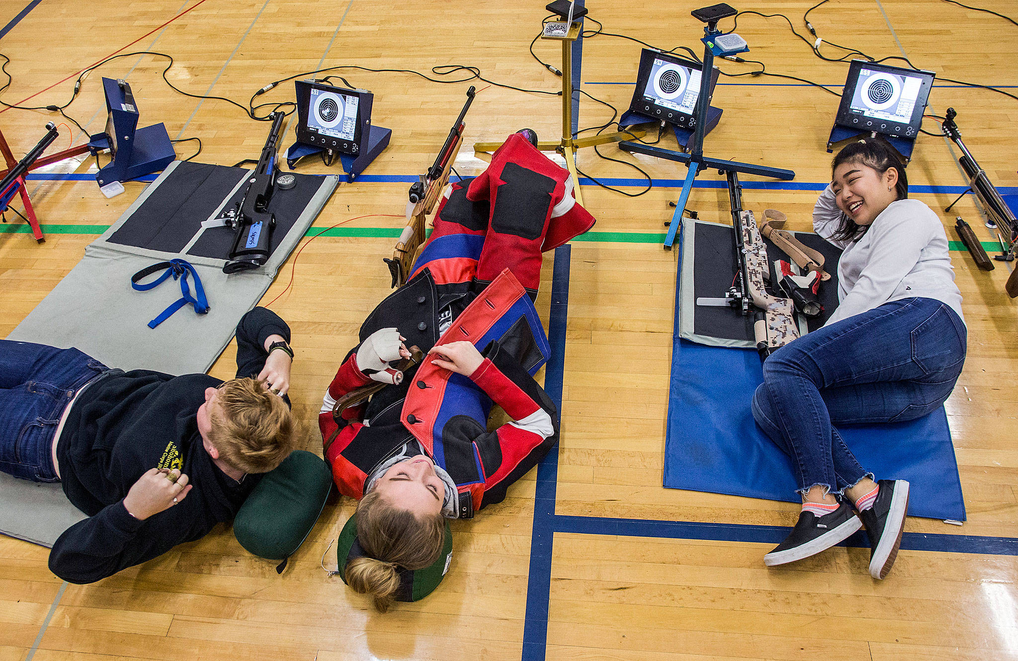 Kayla Dunham (from left), Jesse Brown and Reina Kim take a break during CMP Air Rifle Marksmanship Camp at Snohomish High School on Thursday. (Olivia Vanni / The Herald)