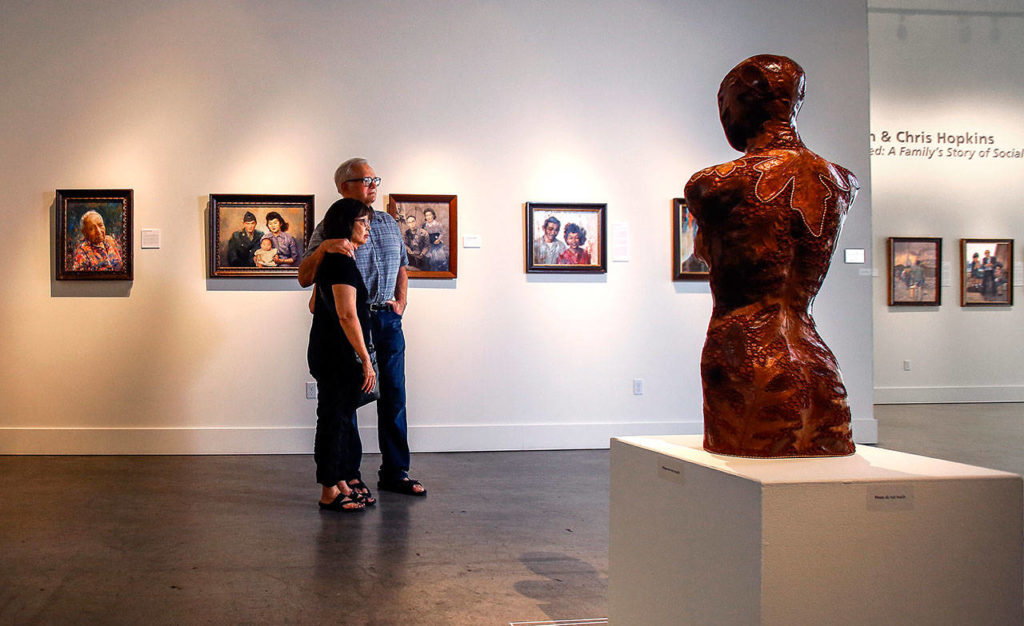 """Chris and Jan Hopkins look over some of the work they have on display in """"Americans Interned"""" at the Schack Art Center in Everett. The renowned couple were named the Schack Art Center's 2018 Artists of the Year. (Dan Bates / The Herald)"""